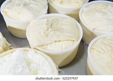 Pieces of fresh cheese wrapped in cloth canvas during the manufacturing process