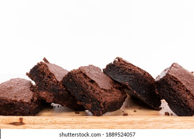 Pieces of fresh chocolate brownie on wooden plate on white background. Stack of fudgy chocolate brownies on white background, homemade bakery and dessert. Brownie chewy squares stack on wooden plate.
