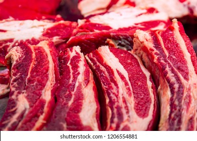 Pieces of fresh crude meat are laid out on a counter of butcher shop