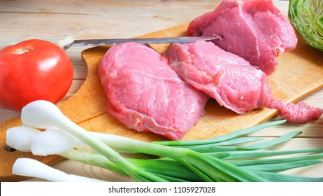 pieces of fresh meat on a wooden desk with spices and vegetables. cooking concept