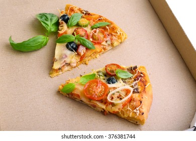 Pieces of fresh pizza on cardboard box closeup