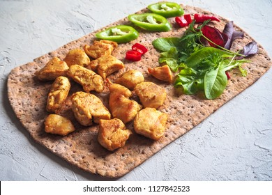 Pieces of fried chicken curry fillet on rye flatbread with vegetables