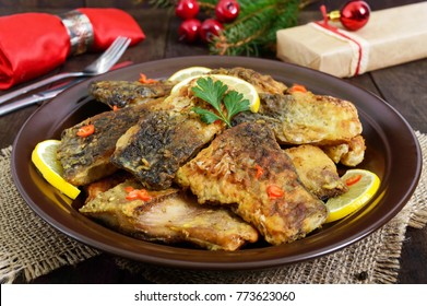 Pieces of fried fish (carp) on a ceramic plate on a dark wooden background.