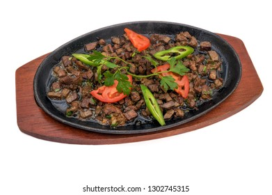 Pieces of fried meat on an iron plate. Asian cuisine