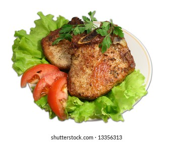 Pieces of fried meat with slices of a tomato on leaves of green salad.
