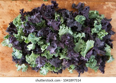 Pieces of green and purple curly kale on wooden cutting board.