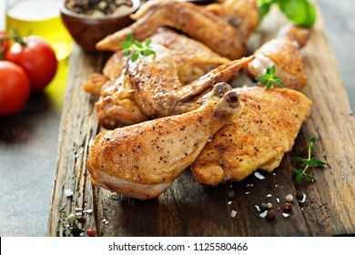 Pieces of grilled or smoked chicken on a wooden board