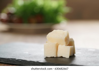 pieces of hard parmesan cheese on slate board, closeup photo