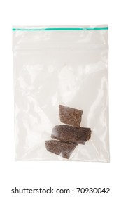 pieces of hashish in a plastic bag , photo taken with a macro lens,  isolated on a white background