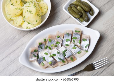 Pieces of herring with onions, gherkins and boiled potatoes