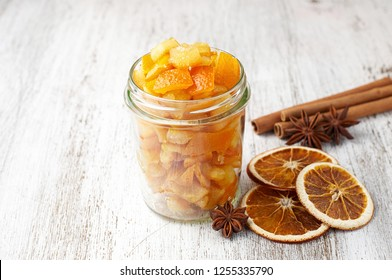Pieces of homemade candied orange peel coated in sugar in glass jar. Close up view with copy space on a white wooden background. Ingredient for traditional Christmas treats