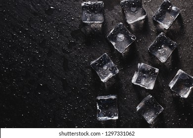 Pieces of ice cubes with water droops on black background. advertising photo
