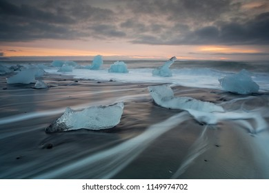 Pieces of ice on the shore of Jokulsarlon beach in Iceland at sunrise. Dramatic sky at sunrise on Jokulsarlon beach in Iceland.