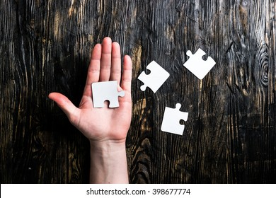 pieces of jigsaw on table and on palm