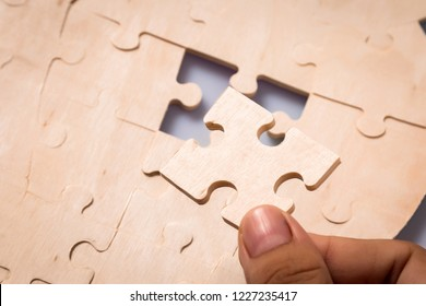 Pieces of jigsaw puzzle in woman's hands