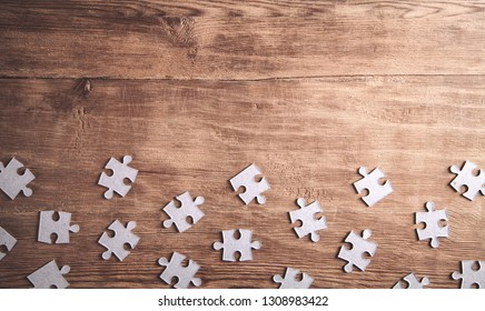 Pieces of the jigsaw puzzles on wooden background.