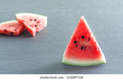 Pieces of juicy ripe watermelon slices on  gray stone countertop