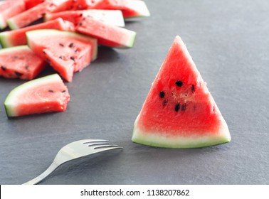 Pieces of juicy ripe watermelon slices with  fork on  gray stone countertop