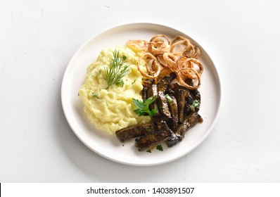 Pieces liver (offal) from beef with mashed potatoes and fried onion rings on white plate over stone background.
