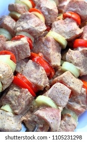 Pieces of marinated raw pork meat strung on skewers with slices of chopped tomatoes and onion with parsley prepared for cooking on barbecue