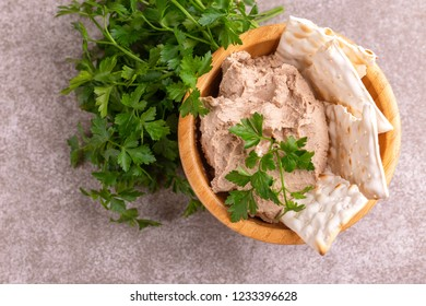 Pieces of matzah with homemade liver pate and parsley on gray marble background. Top view. Copy space