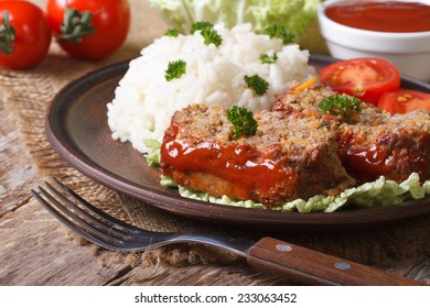 pieces of meat loaf and rice on a plate close-up, horizontal