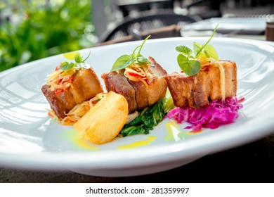 Pieces of meat with vegetables on a white plate. The Restaurant