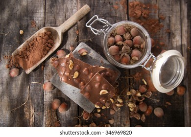 Pieces of milk chocolate with hazelnuts on wooden table