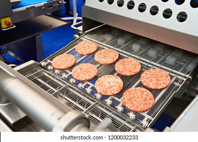 Pieces of minced meat on a conveyor belt machine wet breading