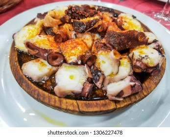 Pieces of octopus tentacles on fair sauce over wood plate