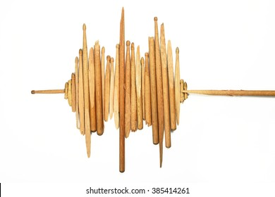 Pieces of old broken used wooden drumsticks in shape of sound wave on white background
