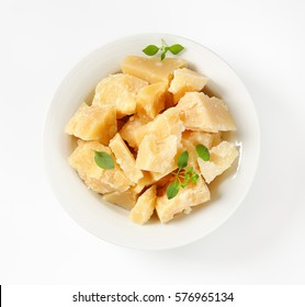 Pieces of parmesan cheese in a porcelain bowl