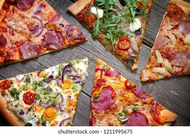 Pieces of pizza of different various types on old retro boards still life concept