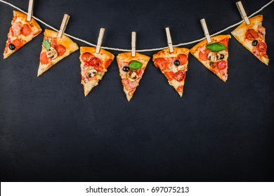 Pieces of pizza in the form of a garland of flags on a dark background. Pizza menu. Conceptual space for text. Billet for the poster of pizzeria.