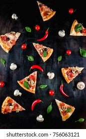 A lot of pieces of pizza with vegetables on a black background. Pizza cooking. Wallpapers with food.
