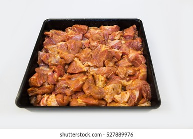 Pieces of pork marinated in spices in a black bowl on a white background, cooking delicious dinner
