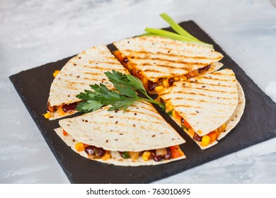Pieces of quesadilla with vegetables and cheese on slate, light background. Vegetarian healthy eating concept.