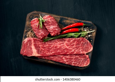Pieces of raw marble beef black Angus for grilling on a wooden Board on a dark background.