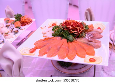 Pieces of red salted fish lie on the plate with salad