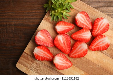 Pieces of ripe strawberries lie on a cutting board on a wooden background.