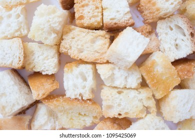 Pieces of roasted white bread on a dark background. Close-up of delicious croutons.