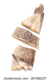 Pieces of salt cod fish isolated on a white studio background.