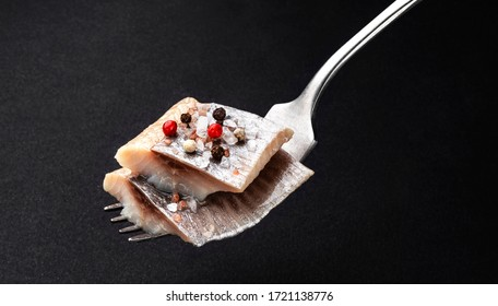Pieces of salted herring on fork on black background, slices of marinated mackerel fish fillet with salt and spices