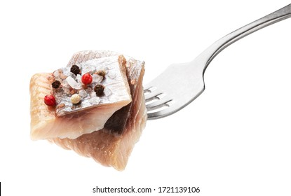 Pieces of salted herring on fork isolated on white background with clipping path, slices of marinated mackerel fish fillet