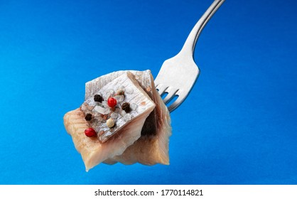 Pieces of salted herring on fork isolated on blue background, slices of smoked marinated mackerel fish fillet