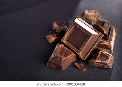 Pieces of tasty black chocolate on a black paper background. Sweet and calorie food.