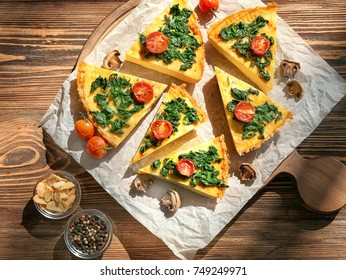 Pieces of tasty frittata with spinach on table