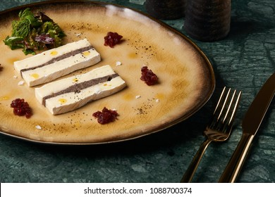 Pieces of Terrine cheese with a layer of meat pate and delicacy snacks on a plate, close-up. Luxury delicious food