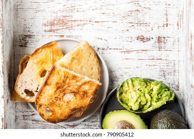 Pieces of toasted white sourdough bread and ripe avocado on rustic background