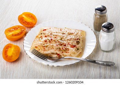Pieces of tomatoes, salt shaker, pepper shaker, chicken aspic in plate, fork on wooden table